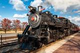 Pociąg z lokomotywą parową opuszczający stację