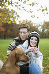 Young man embracing young woman while looking at dog, smiling