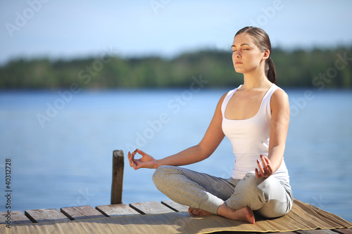 beautiful young girl training yoga near a lake