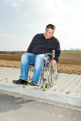 Man with a wheelchair on road pavement
