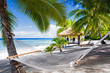 Empty hammock between palm trees on a beach