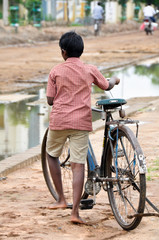 Boy with an adult bike, suburb of Madurai (India)