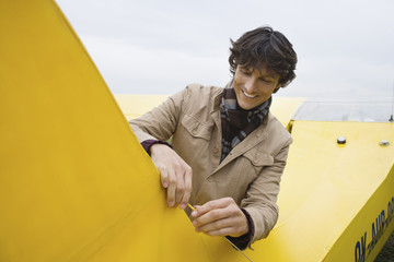 Young man standing by airplane, smiling