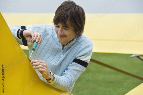 Young man screwing hook in airplane, smiling