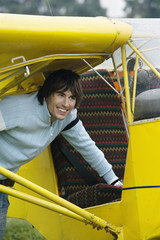 Young man standing by airplane, smiling, portrait