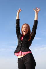 Pretty redhead woman is celebrating with hands up