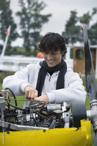Young man screwing in airplane engine