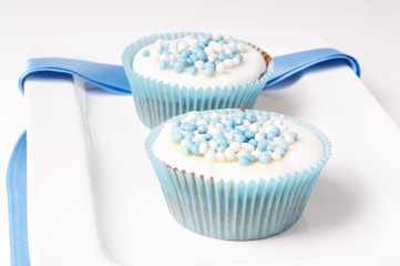 Two baby boy cupcakes on a plate with ribbon