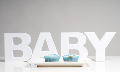 The word baby with two blue cupcakes on a plate