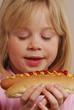 Niña comiendo un perro caliente,comiendo hot dog.