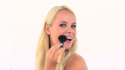 Blonde applying powder on her face