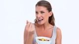 Smiling woman eating a fruits salad