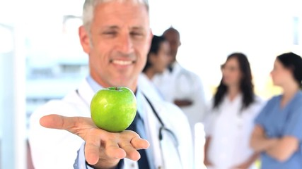 Smiling practitioner showing a green apple