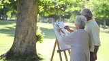Mature couple painting trees