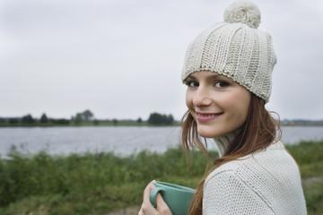 Young woman holding mug, close-up, portrait
