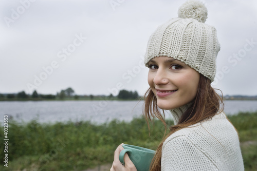 Young woman holding mug, close-up, portrait
