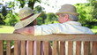 Mature couple wearing hats kissing on a bench