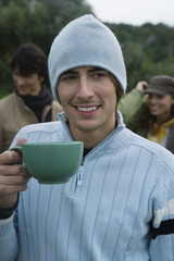 Young man holding mug, smiling