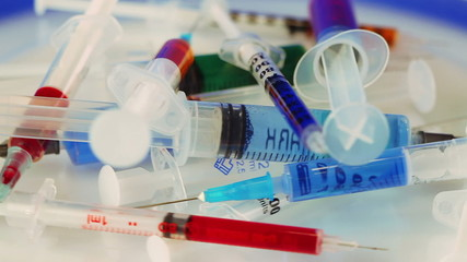Many multicolor syringes rotating on blue (Medical concept)