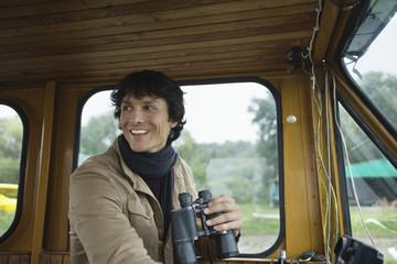 Young man holding binoculars, smiling