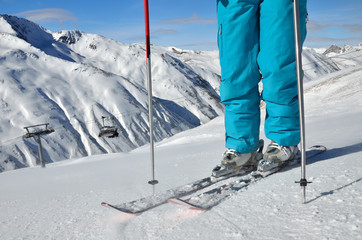 woman's legs in ski boots, standing on skis