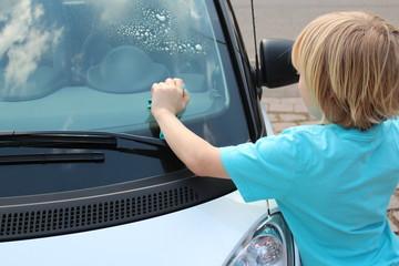 Kind putzt Winschutzscheibe