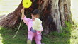 Smiling girl holding a flower and a teddy bear