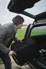 Young man putting bag in car boot, smiling