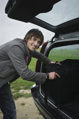Young man putting bag in car boot, smiling, portrait
