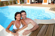 Young smiling couple bathing in private pool