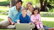 Smiling family sitting on the grass with a laptop