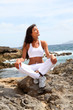 Woman sitting on rocks in fitness outfit