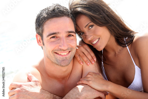 Portrait of romantic couple laying on the beach