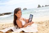 Beautiful woman in bikini using tablet on the beach