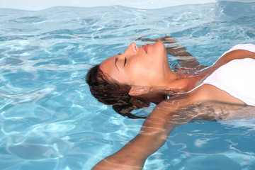 Woman relaxing in swimming-pool