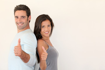 Trendy couple standing on white background with thumbs up