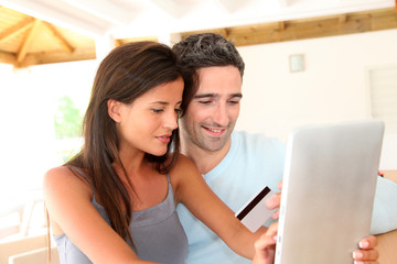 Couple at home doing online shopping with tablet