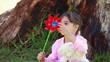 Smiling girl holding a red pinwheel