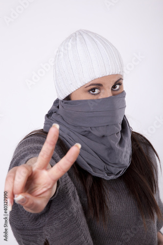 Young masked woman with showing peace sign
