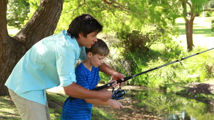 Happy father and son using a fishing rod