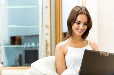Woman working with laptop, at home