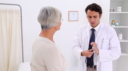 Doctor using his stethoscope on a patient