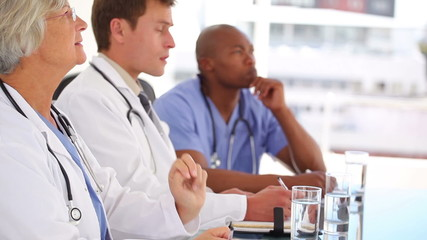 Mature doctor sitting with colleagues