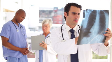 Serious doctor looking at a chest x-ray while standing