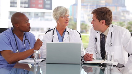 Smiling mature doctor sitting with colleagues in front of a laptop