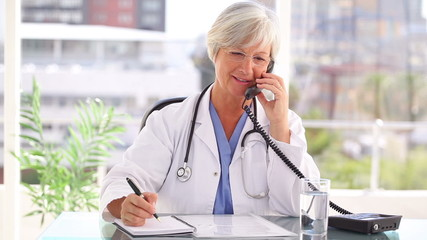 Smiling doctor talking on the phone while sitting