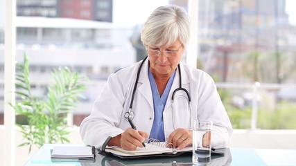 Serious mature doctor writing on her calendar