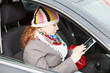 Young woman sitting in car and holding electronic device