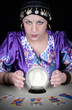 Gypsy fortuneteller uses a crystal ball
