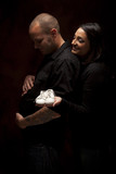 Mixed Race Couple Holding New White Baby Shoes on Black